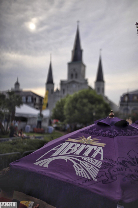 The sun sets behind the clouds and St. Louis Cathedral...Abita Beer tent smiles.