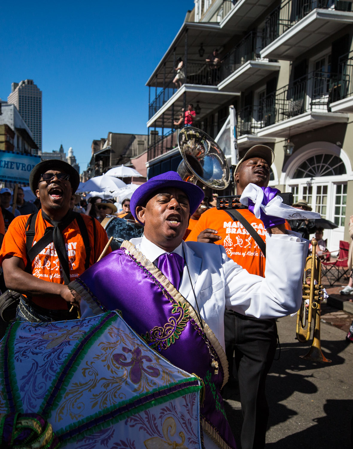 The Mahogany Brass Band marches down Bourbon Street on opening day of the Festival. Band leader Brice Miller sings with trumpet in hand and head raised high.
